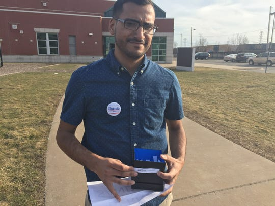 Shiab Mussad, 22, hands out slips of paper in Arabic