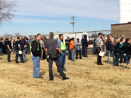 Employees at the International Automotive Components plant at 2500 Highway 6 wait outside on Thursday morning as the Iowa City Fire Department fights a structure fire.
