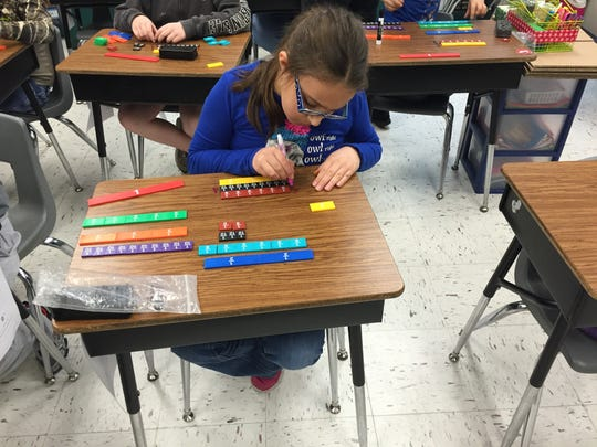 Cayden Manders, a fourth grade student at Craigsville practices equivalent fractions during  a math lesson. Students are encouraged to write on their desks with dry erase markers to help them study.