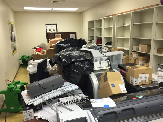 Boxes, supplies and computers litter a room at Adams