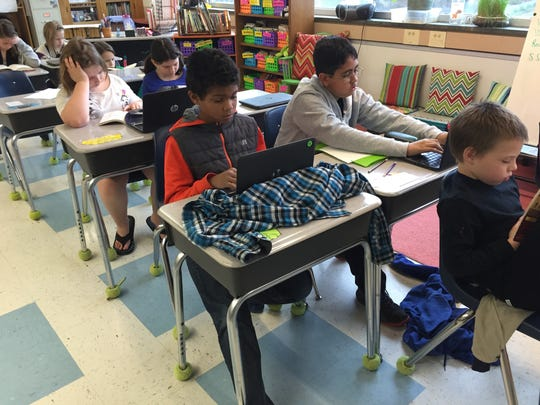 Fourth grade students at McSwain Elementary School complete writing exercises on laptops on Monday.