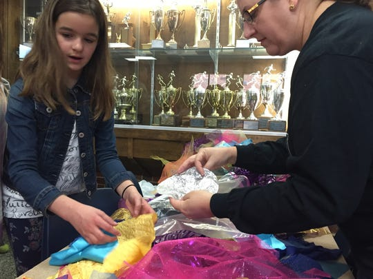 """A volunteer helps student Bonnie Rossen pick out the pieces of fabric to form her costume for """"The Little Mermaid"""" on Saturday, March 12, 2016."""