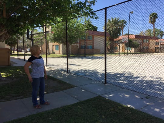 Leticia Valencia, a mother of six, stands near the basketball court at Summer Field Apartments where she often watches her kids play.