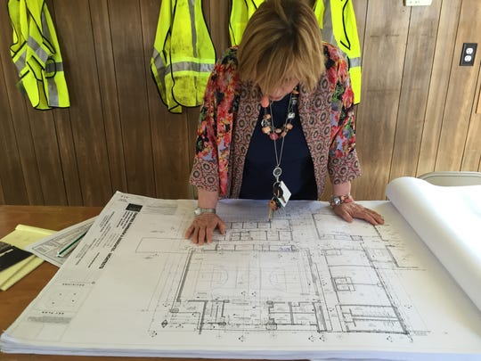 Principal Mindy Garber looks over plans for the new school.