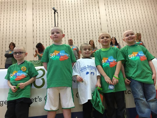 Students show off their shaved heads during a St. Baldrick's Day fund-raiser Wednesday, March 17, 2016 at Kennedy School in Roxbury. The students raised about $15,000 this year.