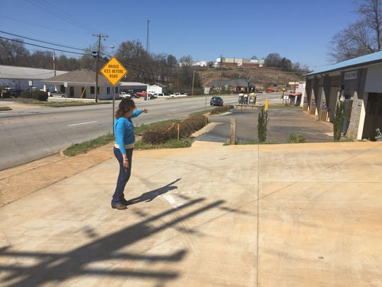 Starr Pajela, owner of the Blue Flame Car Wash in Pickens, shows where the new turning lane on Jones Street will cut into her property, marked in white paint.