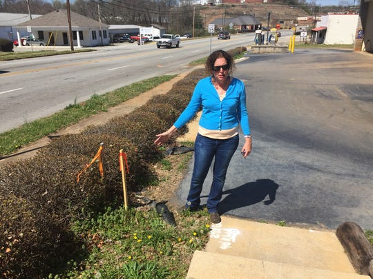 Starr Pajela, owner of the Blue Flame Car Wash in Pickens, shows where the widening of Ann Street will cut into her property.