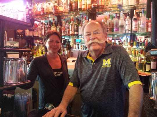 Champ's Pub owner David Beauchamp is a big-time University of Michigan fan. Standing next to him is bartender Mindy Fischer.