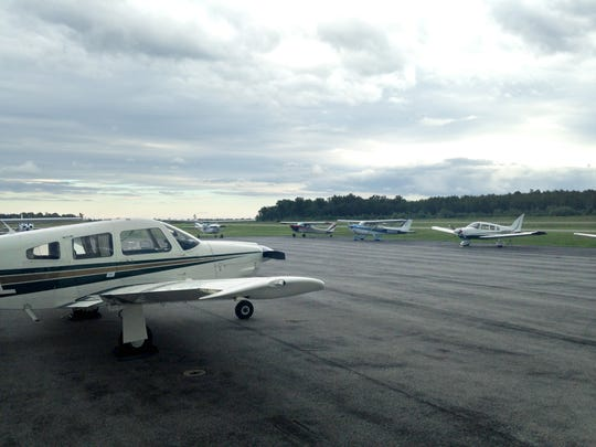 Recreational aircraft sit in a Canandaigua airport lot.