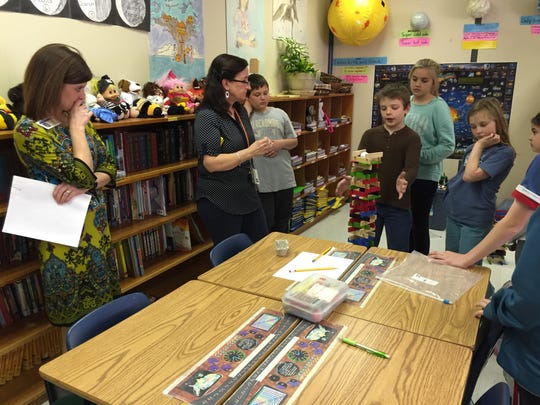 Principal Miranda Ball (left) and fourth grade teacher Cathy Moyers-Youell listen to students talk about a STEM project where they were asked to build a tower that could support two golf balls.