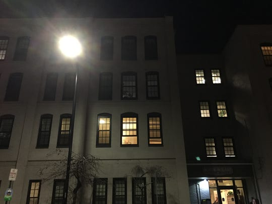 Second-floor windows are illuminated in the apartment building at College and Pine streets in Burlington, where police shot a man Monday night.