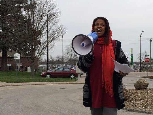 Mazahir Salih, the president of the Center for Worker Justice of Eastern Iowa, leads a group of activists in a call for a higher minimum wage outside North Liberty City Hall on Tuesday.
