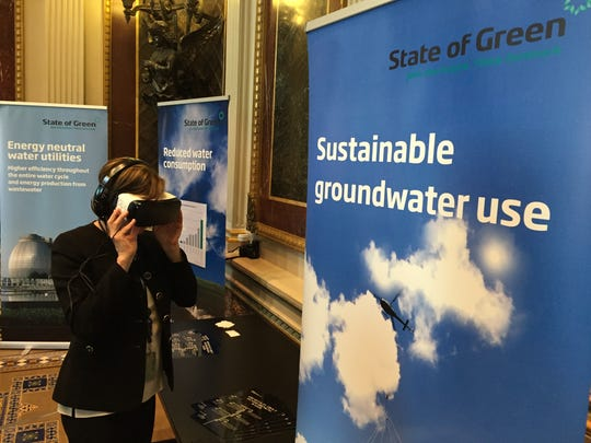A participant in the White House Water Summit takes a virtual tour of a wastewater plant in Denmark using a VR headset.