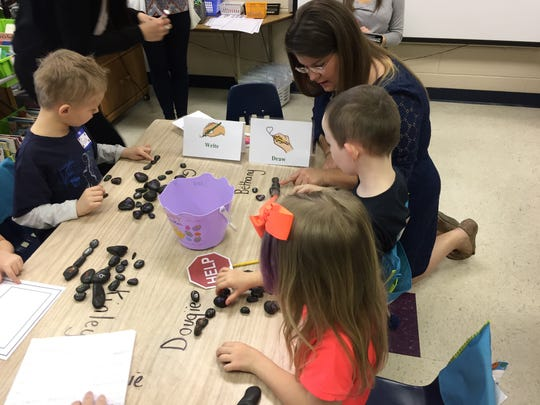 Kindergarten teacher Stacy Truslow works with students on literacy. Each rock has a word on it and students line up the rocks to make sentences.