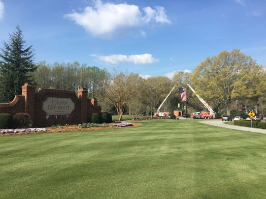 Ladder trucks from Duncan Chapel Fire Department raise a flag over the entrance to Furman University in honor of Officer Allen Jacobs