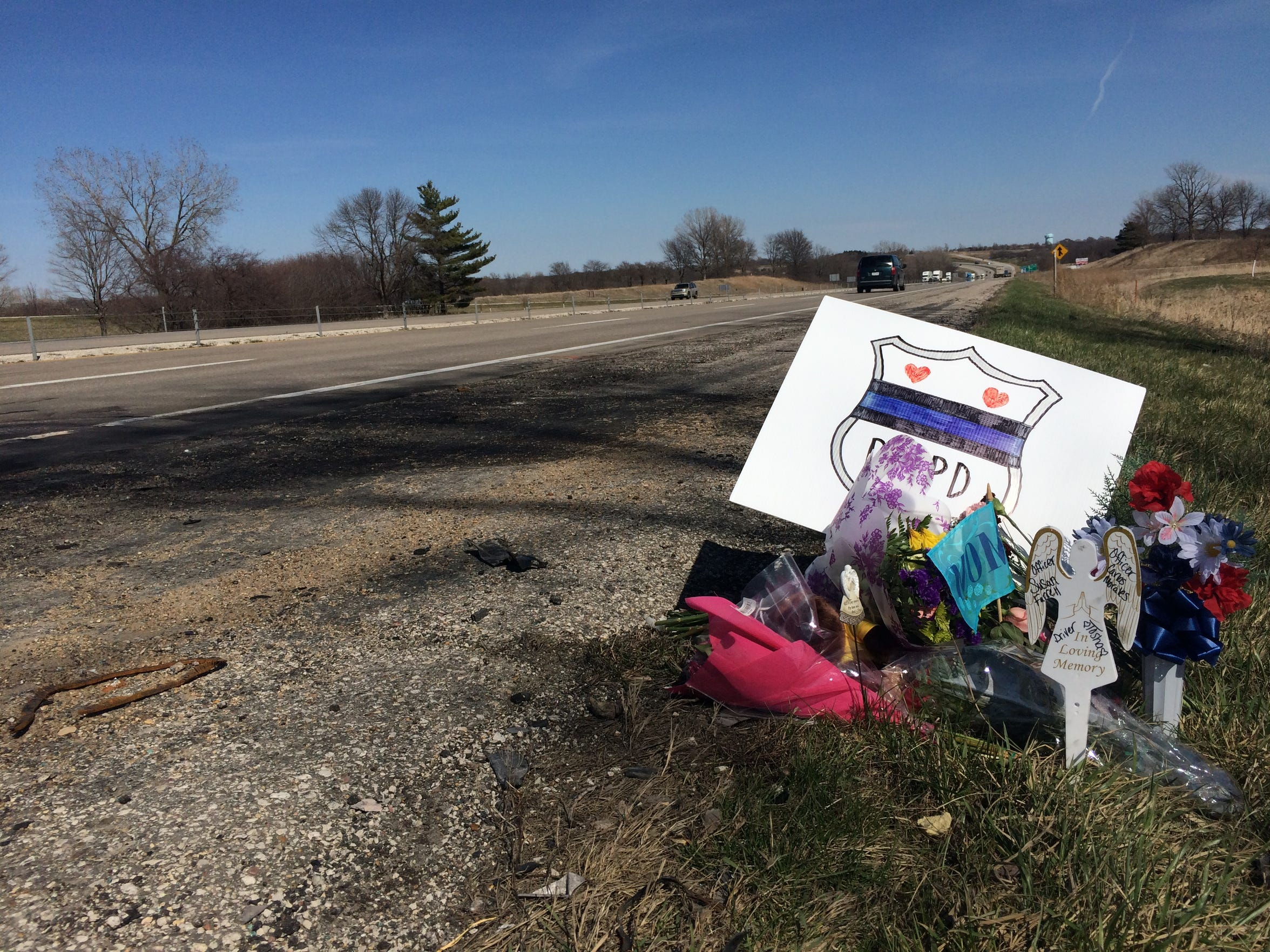 A file photo from March 2016 shows a memorial that marked where a fiery Interstate Highway 80 wreck occurred. Four people were killed in the wreck, including two Des Moines police officers.