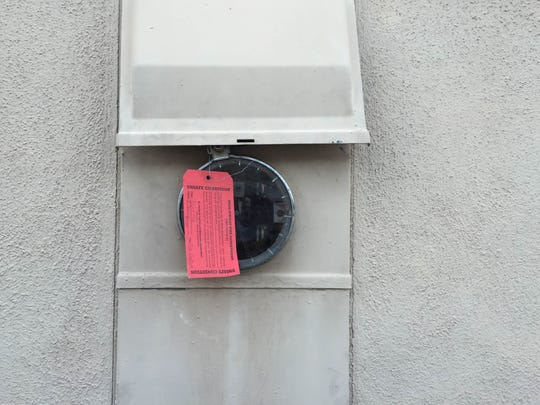 A tag on the electrical meter at a house in Palm Springs identifies it as unsafe after an electric shock in a pool on March 27.