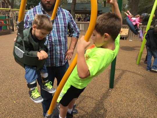 Silas Owens, 3, father Jared Owens, and a new friend tried out the double swing inside the updated Benny Russell Park.