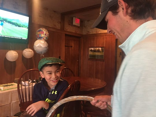 Assistant Westbrook Country Club pro Jake Houston presents 9-year-old Charlie Danuloff with a green golf cap and gift basket at his surprise send-off party Wednesday. Charlie is competing Sunday in the national Drive, Chip and Putt  skills contest at Augusta National in Georgia as a lead-in to the Masters Tournament.