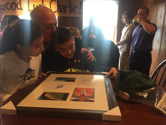 Bill Danuloff shares a moment with his grandkids Paige and Charlie as they look at a framed collage of pictures presented to Charlie during Wednesday's surprise send-off party. Charlie is competing Sunday in the national Drive, Chip and Putt skills contest at Augusta National in Georgia as a lead-in to the Masters Tournament.