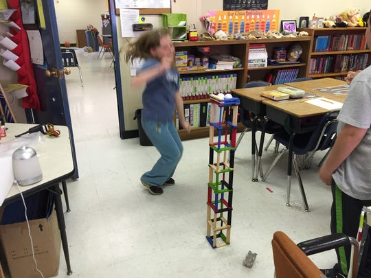 Fourth grader Evelyn Boody jumps for joy after she and her partner won the tallest tower race in Cathy Moyers-Youell's class.