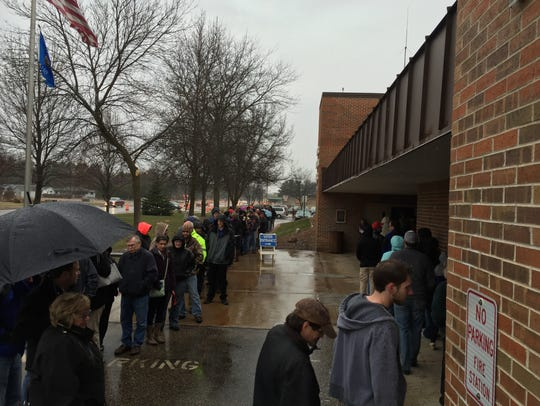 Residents wait in line Tuesday to vote in the village