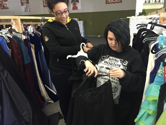 Emily Chase, right, a senior at Community High, gets help from her friend Shayla McPherson as she looks for a prom dress.