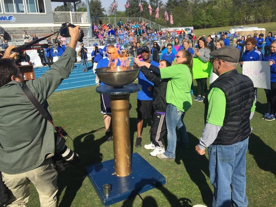 A participant in the Special Olympics gets some help with lighting the torch during the opening ceremony Wednesday at Southern Wesleyan University.