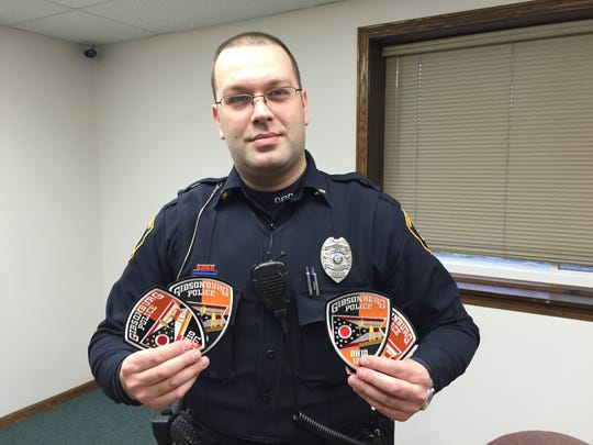 Gibsonburg office Mike Senyo, shown here displaying a new uniform patch he designed for department, administered naloxone to himself after being exposed to a suspected opioid during a traffic stop on April 19.