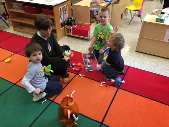 Jelisa Wolfe, director of the preschool and director of student services, plays Mr. Potato Head with Kate Tacy's preschool students on Thursday.