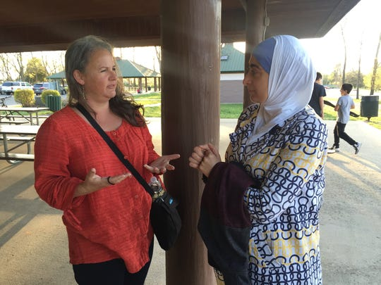 Laurie Watts, left, and Noor Kattih talk at the Love Your Neighbor interfaith picnic on Sunday at Barfield Crescent Park.