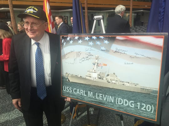 Retired U.S. Sen. Carl Levin stands on Monday, April 11, 2016, next to a photo of the Navy destroyer that will bear his name.