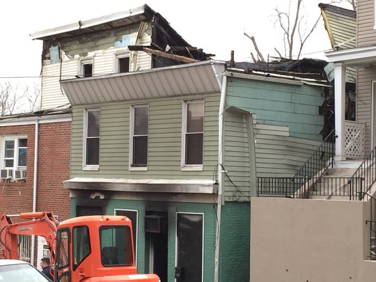 A demolition crew on the scene the day after the April 10, 2016, fire that damaged three houses on Herriot Street in Yonkers. The fire started in 53 Herriot, the green house and spread to the houses on either side.