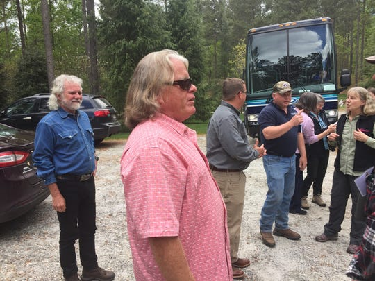 Chuck Leavell, left, joins a bioenergy tour at the farm of Tom O'Hanlan, center, with a group of European  sustainable energy experts.