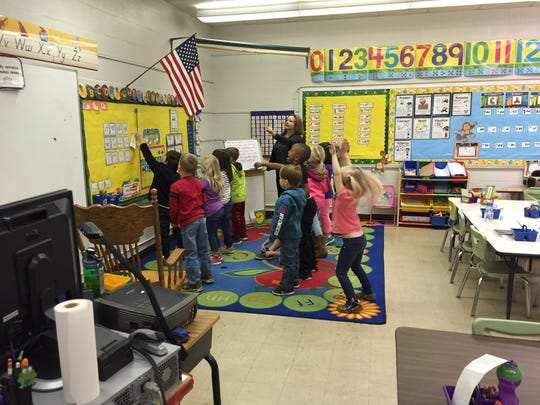 Kindergarten students incorporate movement into a literacy lesson on Wednesday morning.