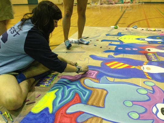 Sara Head, a junior at Bolton High School, helps her group complete a chalk drawing of Blue Dogs during the school's 12th annual chalkfest on Friday.