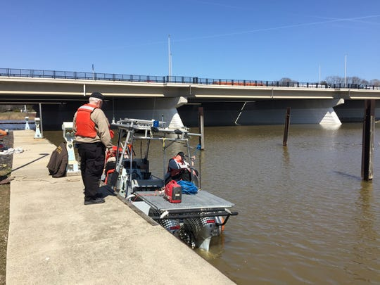 Dive team members prepare sonar equipment to search the Black River for a reported bridge jumper.