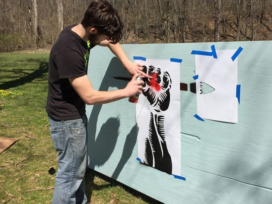 Lucas Parsons works on an installation panel at North Lake Park celebrating public art.