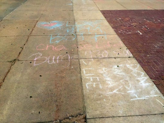Chalked messages from the organization Students for Life at the University of Iowa line the T. Anne Cleary walkway on Monday before being washed away by Tuesday's rain. UI officials removed similar chalked messages the week before, saying that they violated UI policy. Officials now say that the policy is ambiguous and will be revised.