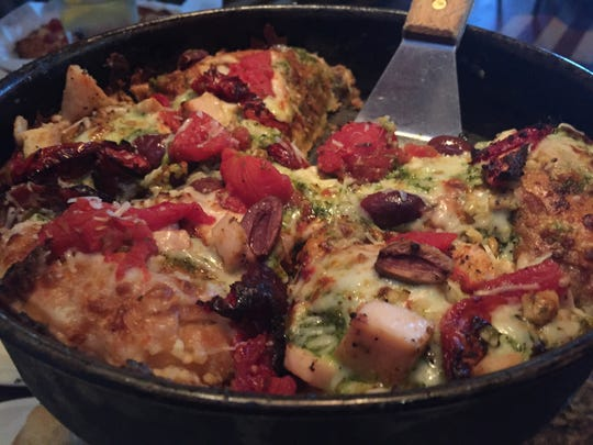Deep dish pizza is loaded with  grilled chicken, basil pesto, roasted garlic, Kalamata olives, sun-dried tomatoes, and feta cheese.