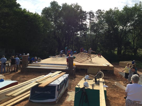 Volunteers from the Golden Strip Church Coalition begin to build Nakita Bouie's new Habitat home Thursday in Simpsonville.