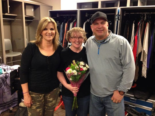 Teresa Shaw (center), of Mason City, visited country stars Garth Brooks and Trisha Yearwood backstage in Omaha last May.