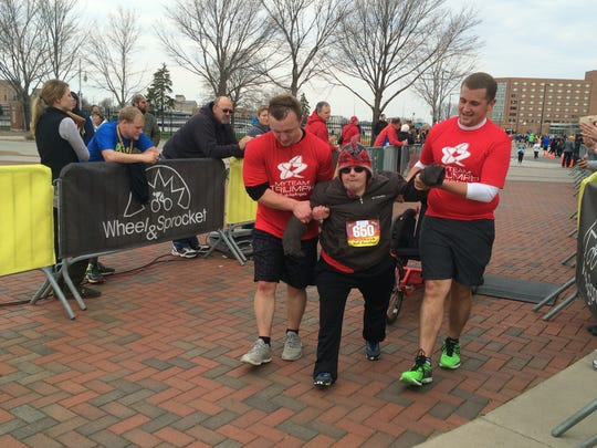 Nathan Gross, middle, crossed the finish line of the half marathon. Gross, who has a physical challenge, participated as part of TEAM TRIUMPH.