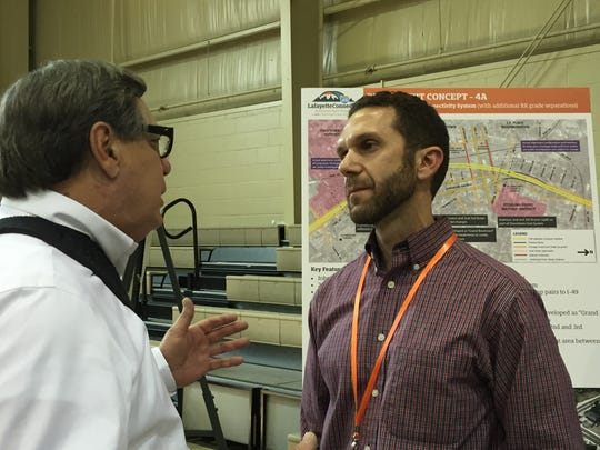 Lafayette resident Martial Broussard, left, who put tape over his mouth at a March meeting after he was prevented from asking questions about the I-49 Lafayette connector project, speaks with project manager Toby Picard of the Louisiana Department of Transportation and Development on April 27, 2016, in Lafayette, LA.