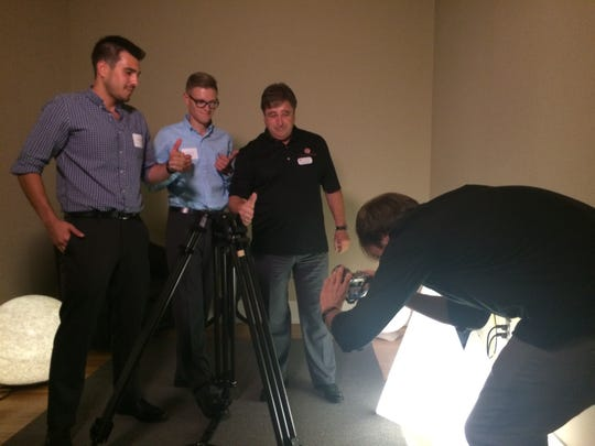 From left: Guillermo Fernandez and Tyler Whitman of Lithos Tripod get their picture taken with Dieter Kondek, co-founder and CEO of The Rocket Lounge.