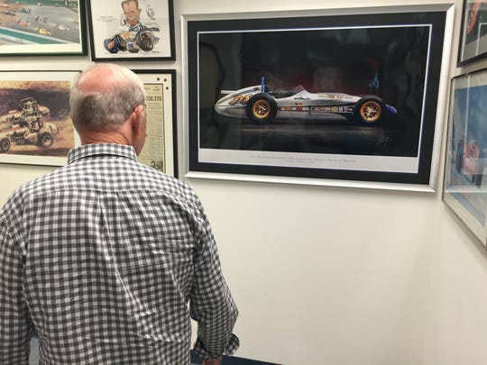 Parnelli Jones looks at artwork hanging in his office hallway, including this illustrating his 1963 Indy 500 winner.