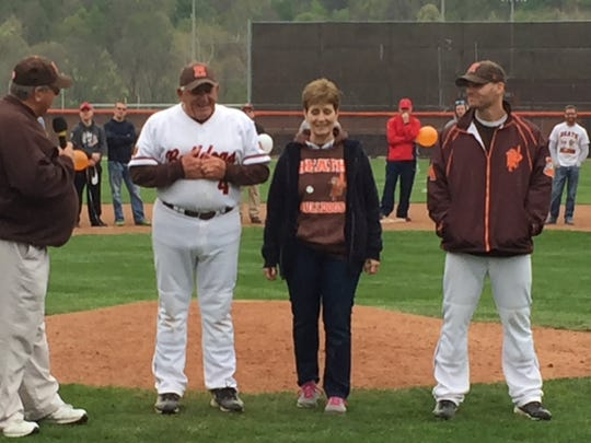 Retiring Heath baseball coach Dave Klontz, his wife Sheila and son Adam take center stage at Dave Klontz Field on Saturday. With his former players lining the infield, Klontz was honored for his 45 years as Bulldogs' coach.