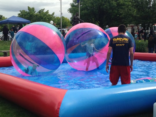 Children play inside floating plastic balls Saturday