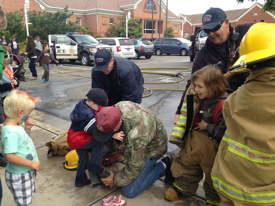 Firefighters help children put on overly large turnouts