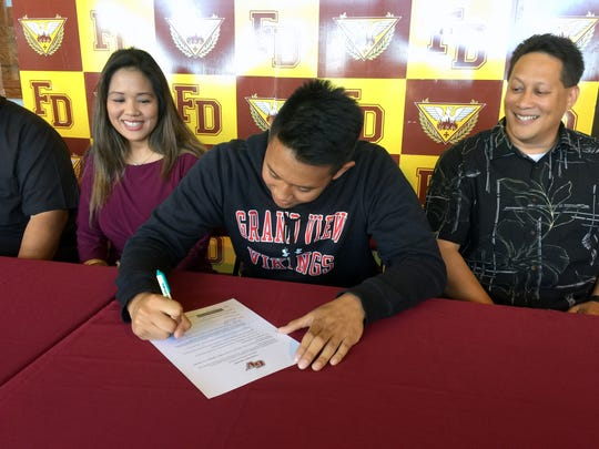 Father Duenas Friar' Eric Ada signed his letter of intent to play for the Grand View Vikings on Monday, May 2 at the Father Duenas Phoenix Center. Watching over him are his mom Katherine Ada and dad Herman Ada